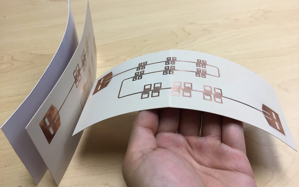 Printed thin, flexible LiveTag tags in comparison with a piece of photo paper