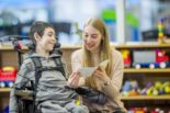 Woman reads to child in wheelchair