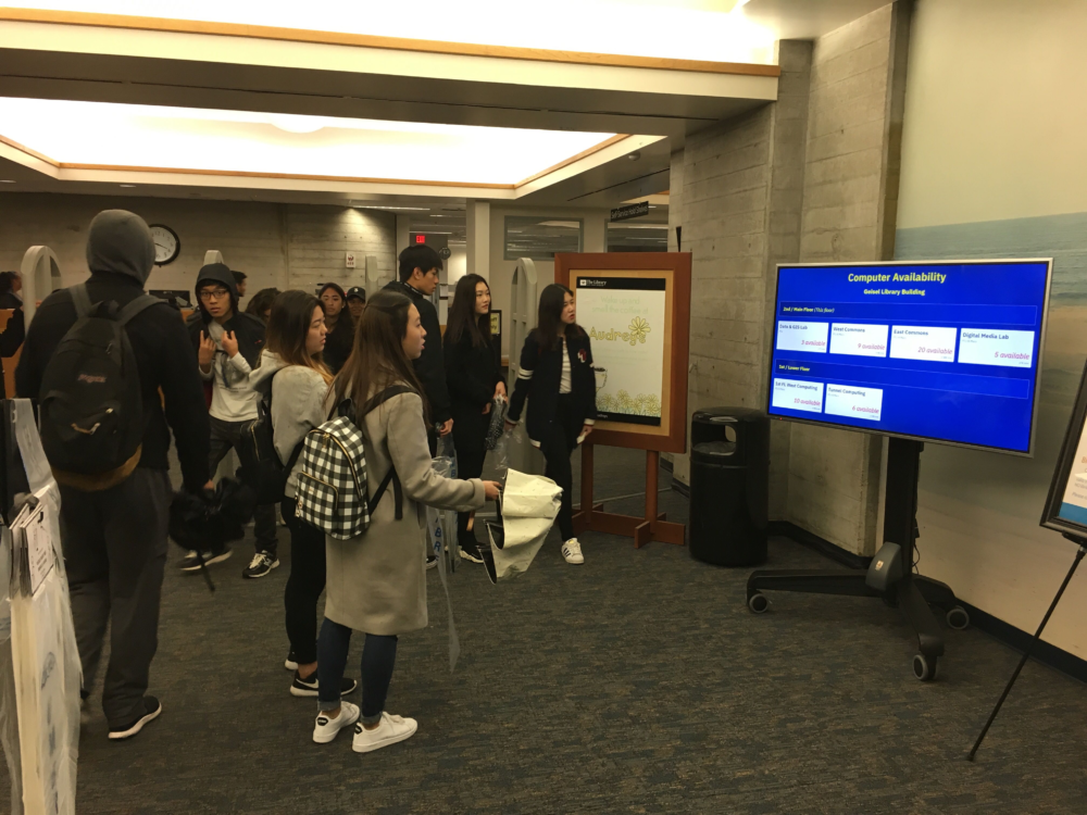 students viewing a chart that lists available computers in the UCSD Geisel Library