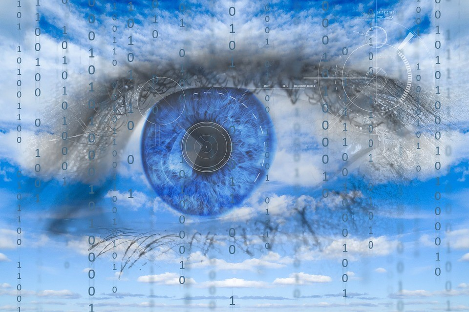 A giant blue eye with lines of binary code written over it