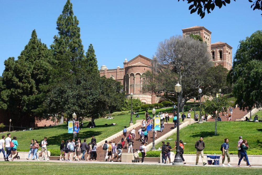 Students on the UCLA campus, with the Janss Steps and Royce Hall in the background.
