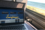 A laptop open to the surfliner website, on an Amtrak train, the Pacific Ocean is outside the window.