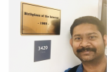"Pranay Bhattacharyya stands next to the ""Birthplace of the Internet"" plaque in Boelter Hall"