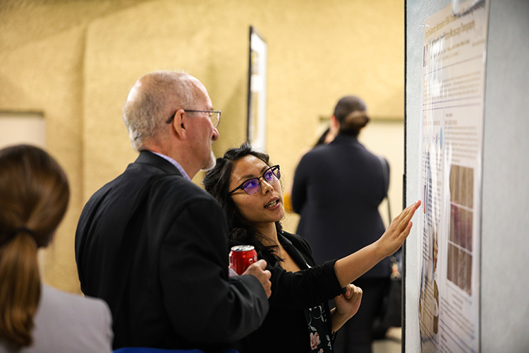 Two people looking at a whiteboard, talking