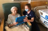 A nurse helps an elderly patient read a tablet in the hospital