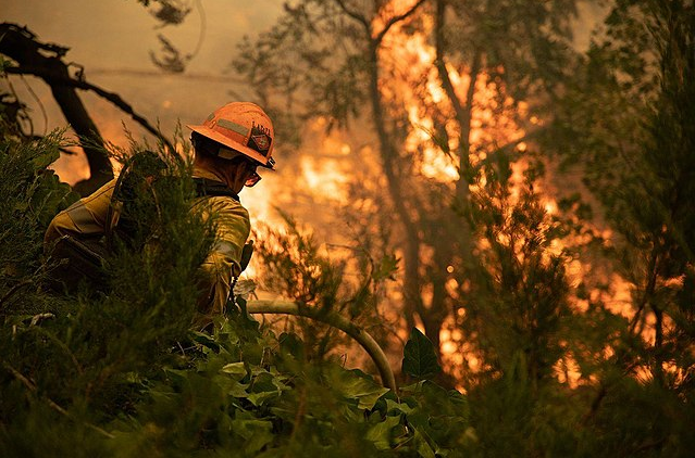 A firefighter walking towards a wildfire