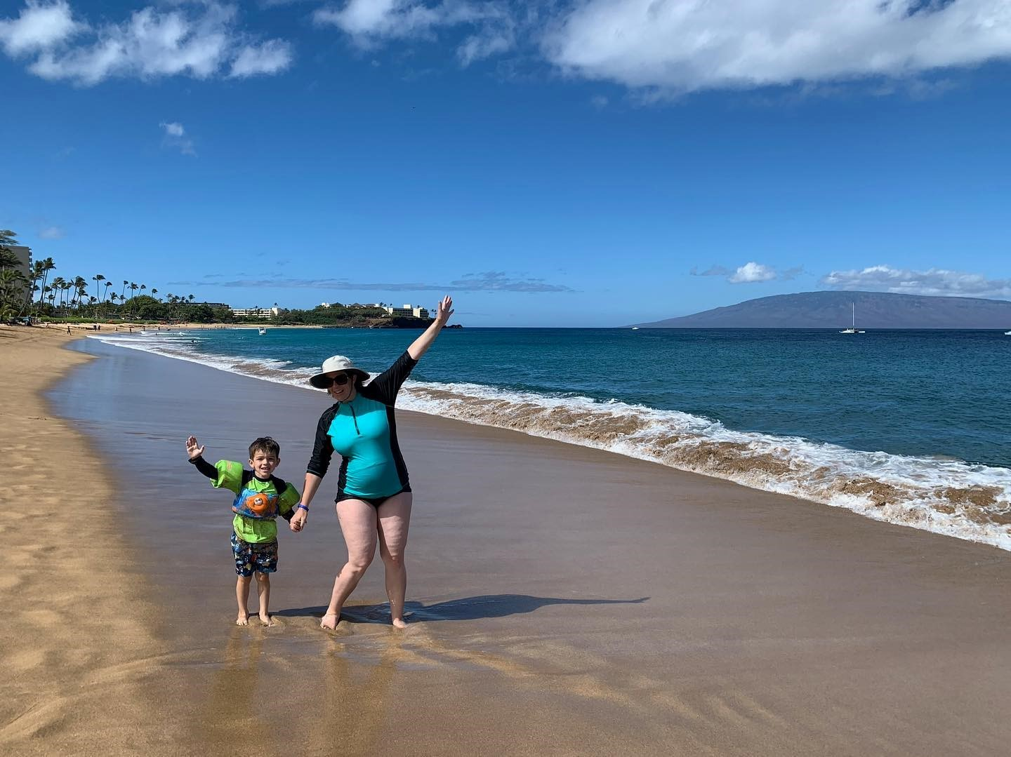 A mom and her son playing on the beach